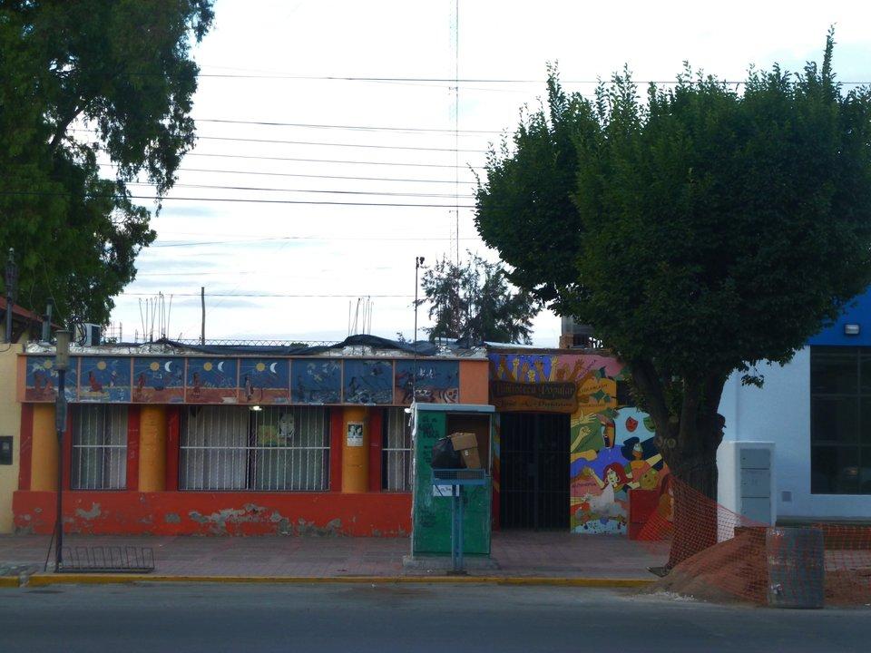 "Biblioteca Popular ""José A. Pujadas"", frente a la plaza principal."